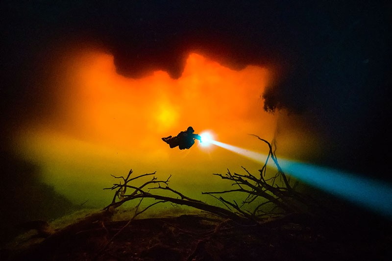 A diver swims in a cavern