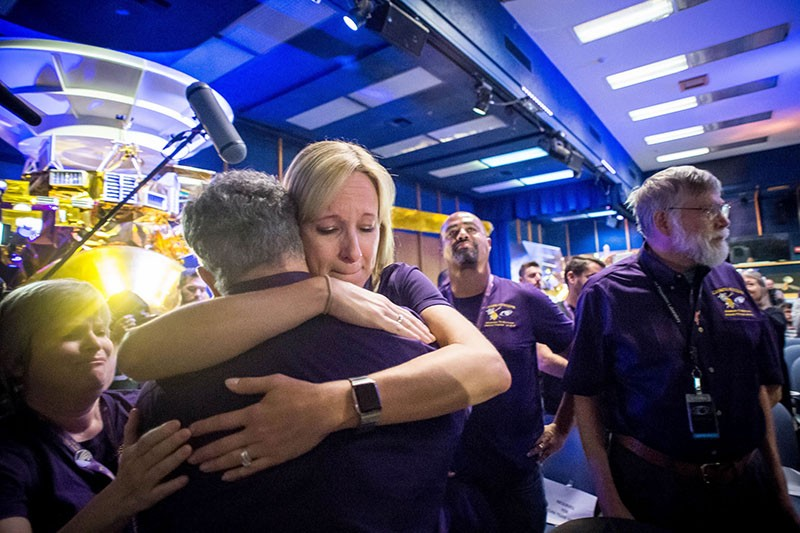 Scientists and Cassini team members hug