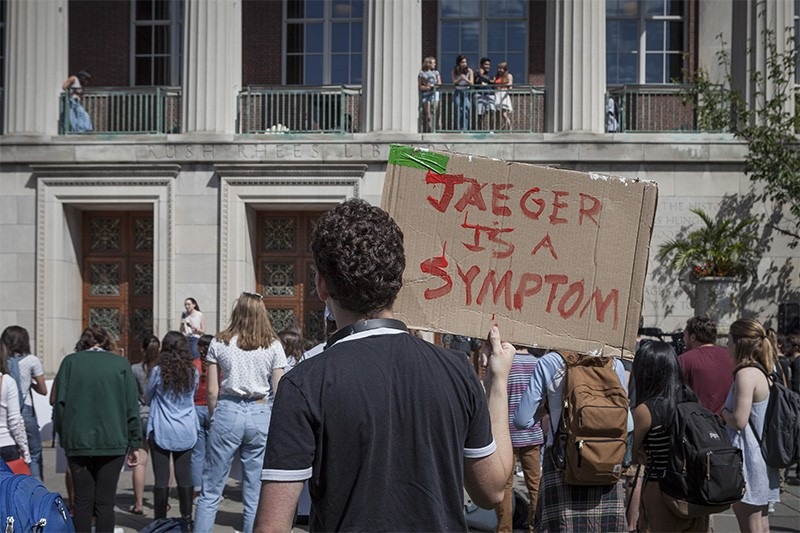 Man holds sign reading 'Jaeger is a symptom' at a rally at Rochester University in Sept. 2017.