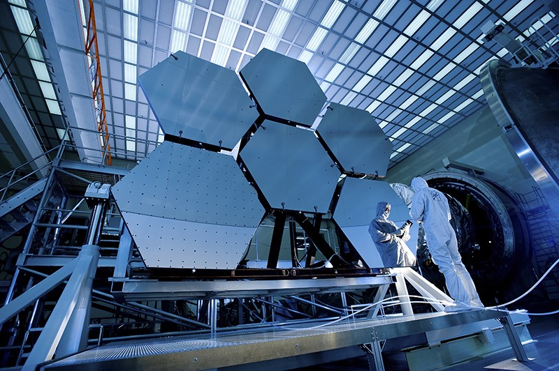 NASA engineer examining mirrors on the James Webb Telescope.