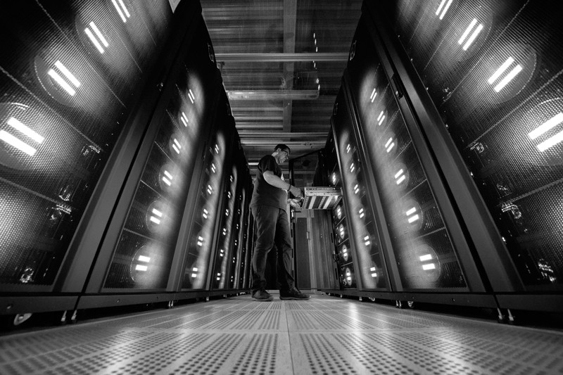 A worker poses next to a supercomputer