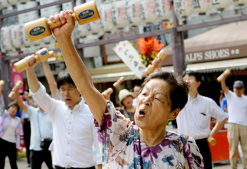 An elderly lady participates in a group exercise class.