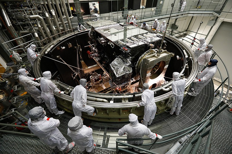 Many people in white clean suits stand around a piece of machinery, a satellite in thermal vacuum testing.