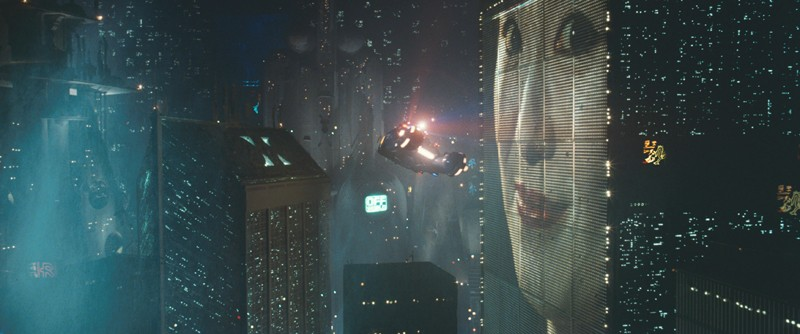 In a futuristic cityscape, a vehicle hovers in front of a screen showing a woman's face.