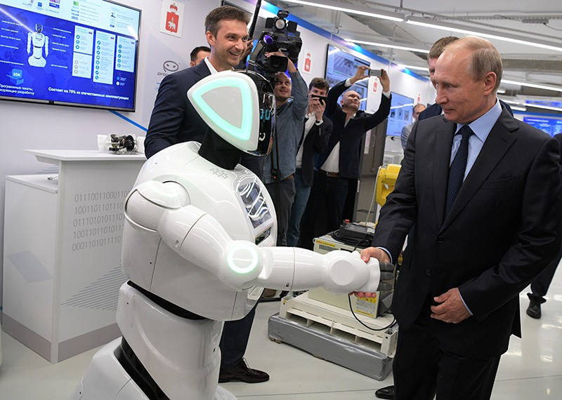 Vladimir Putin shakes hand with a robot at an exhibition at ER Telecom in Russia, 2017