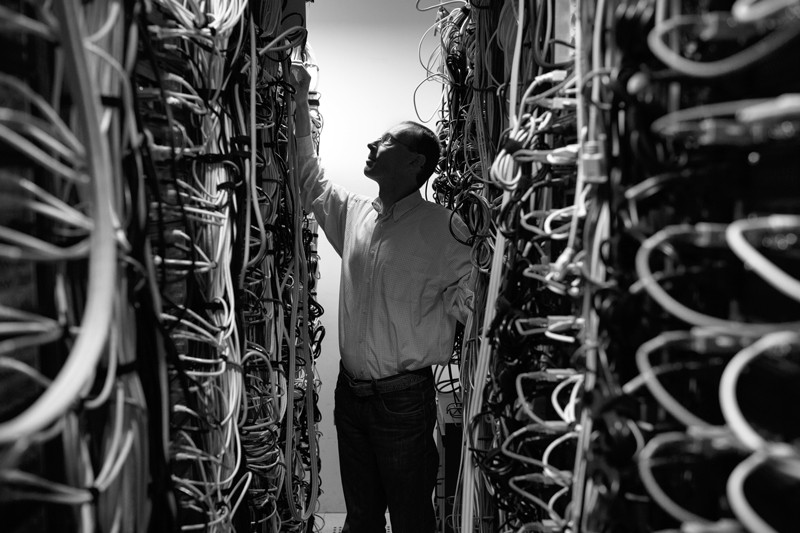 A man checks the wires of a data storage device