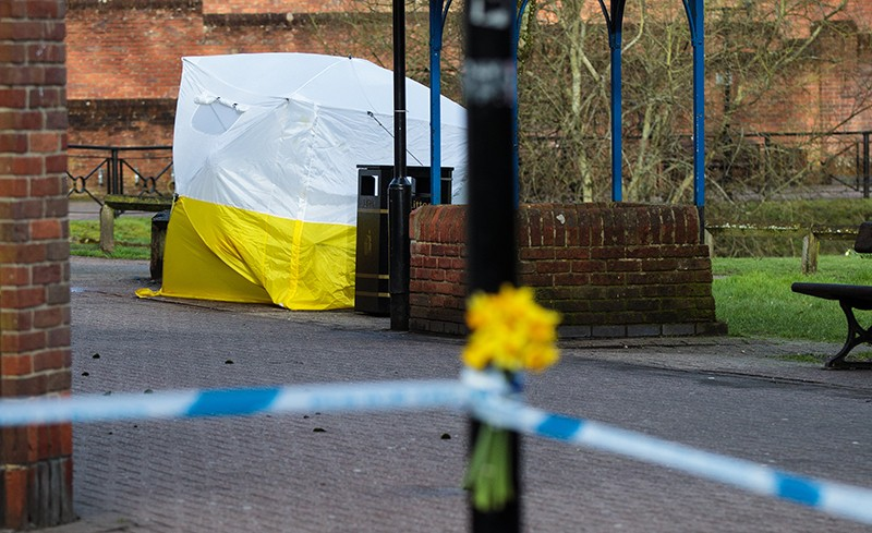 Flowers are pictured in front of a police forensics tent covering the bench connected to the Sergei Skripal nerve agent attacks