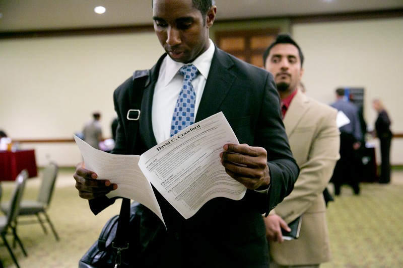 A jobseeker reviews his resume at a careers fair