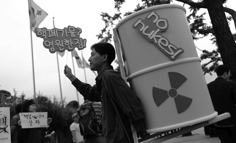 Protester carrying nuclear waste drum in anti-nuclear power protest