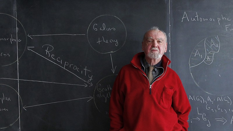 Robert Langlands stands in front of a blackboard covered with equations.