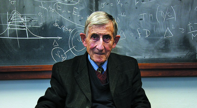 Freeman Dyson, an elderly white man, sits in front of a blackboard covered in mathematical notation.