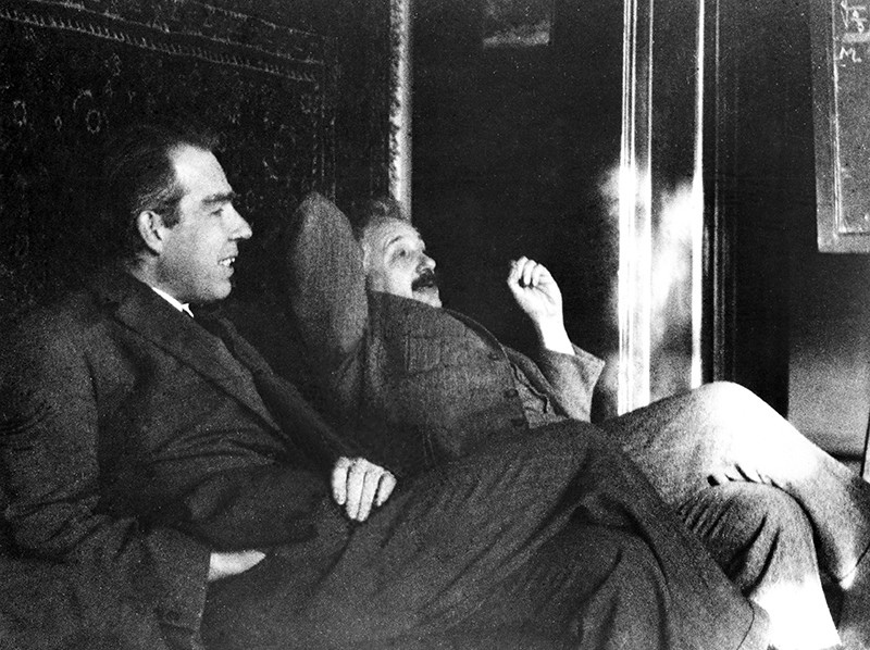 Black and white photo showing Bohr and Einstein sitting side by side in conversation.