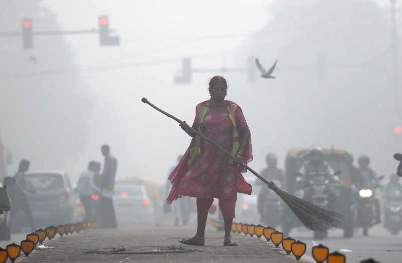 A street cleaner works in heavy smog in Delhi