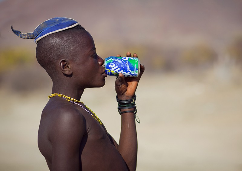 Muhimba young man with traditional hairstyle drinking a can of sprite in Iona, Angola
