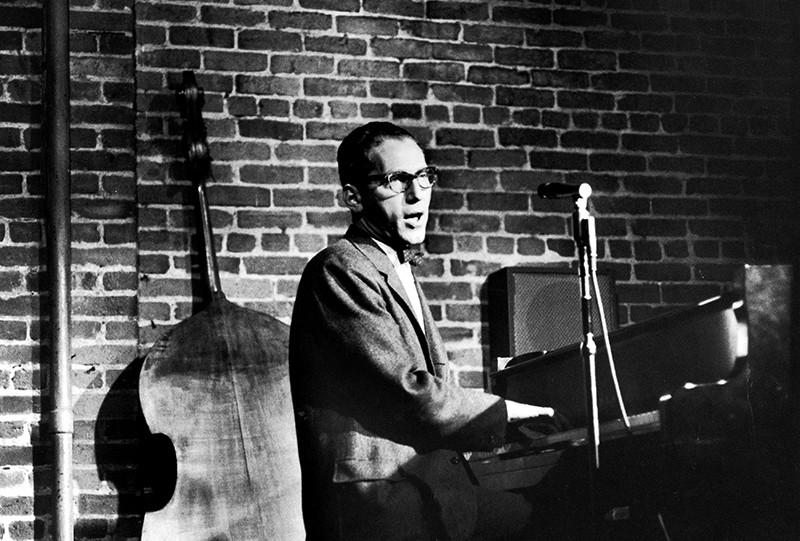 Black and white image of a white man in glasses playing the piano and singing, with a double bass in the background.