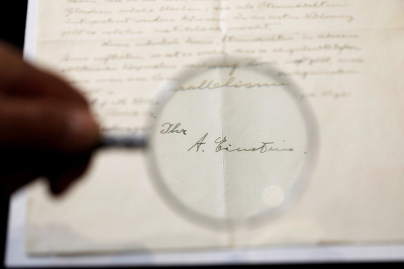 Magnifying glass showing signature of Albert Einstein