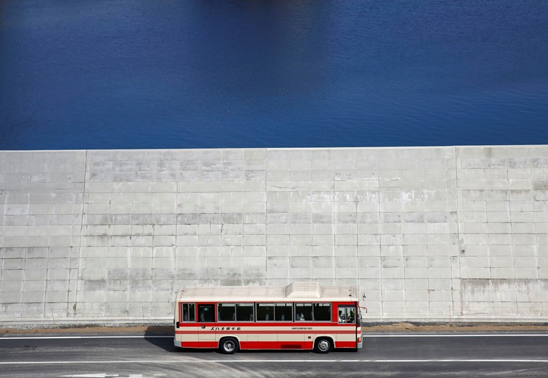 A bus is driven past a seawall