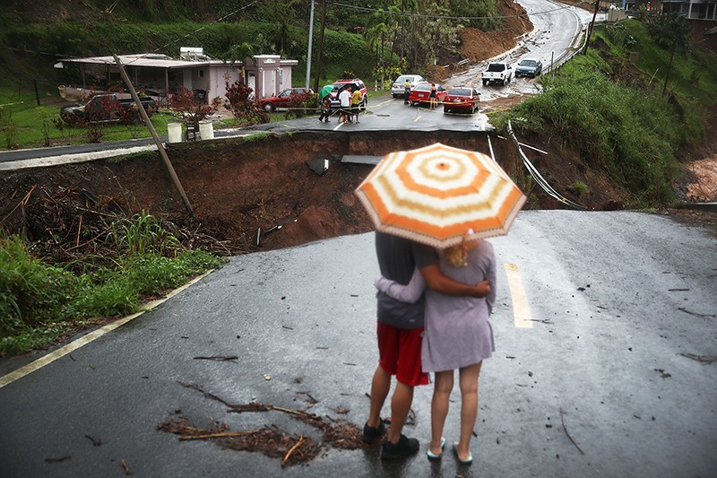 People under an umbrella look at a section of collapsed road that continues to erode after Hurricane Maria swept Puerto Rico.