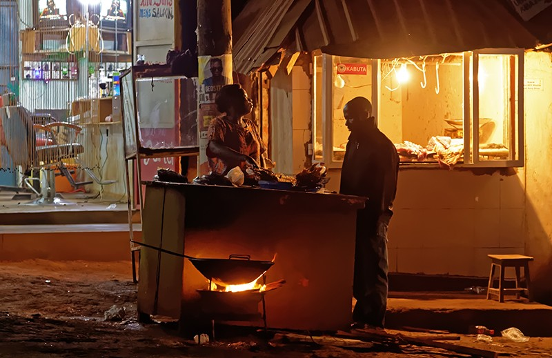 A street vendor prepares food after nightfall in Wakiso District of Uganda.
