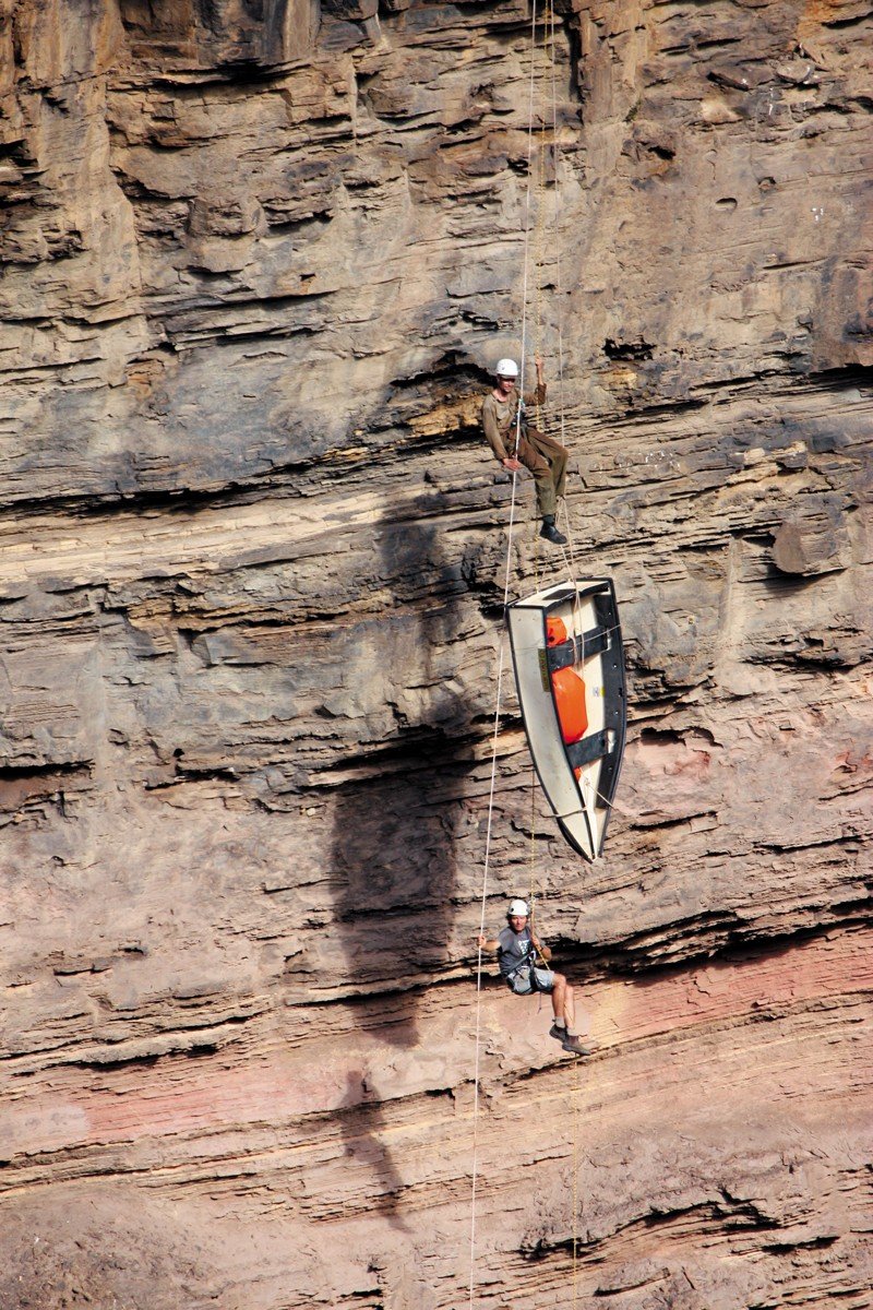 Two men and a boat hanging from rope on a cliff face