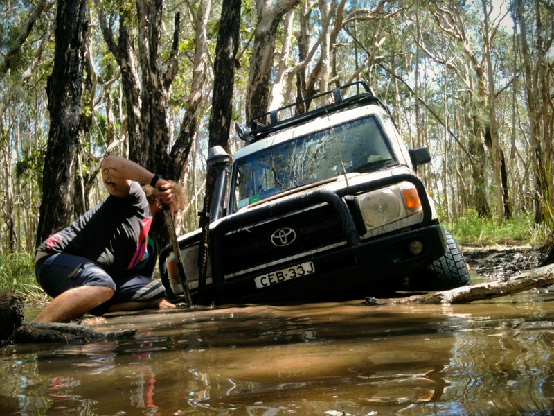 Man trying to dig a 4x4 out of a puddle