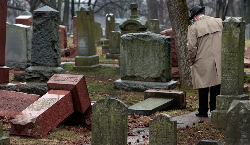 A passer-by looks at topped gravestones in a Jewish cemetary