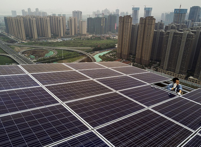 A worker from the Wuhan Guangsheng Photovoltaic Company talks on his phone as he works on a solar panel project in China, 2017.