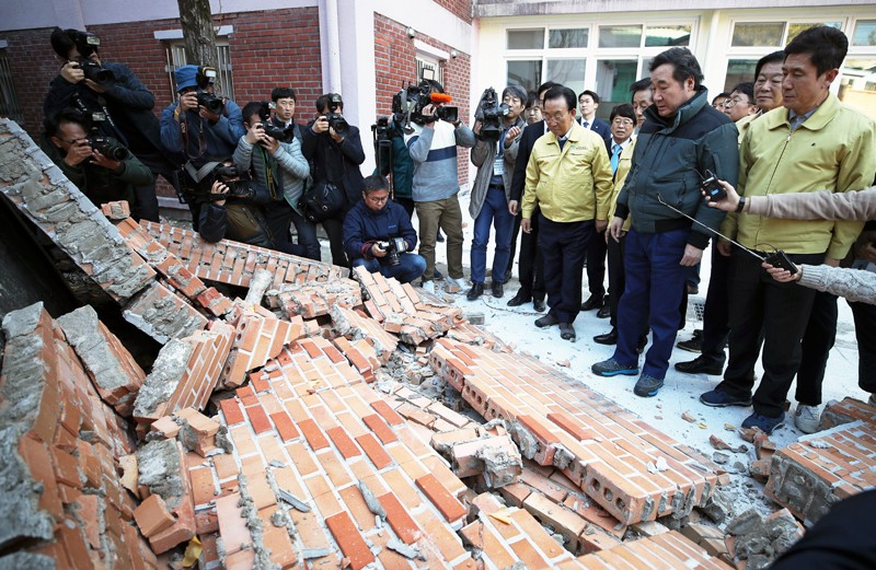 Crowd inspects damaged buildings after earthquake