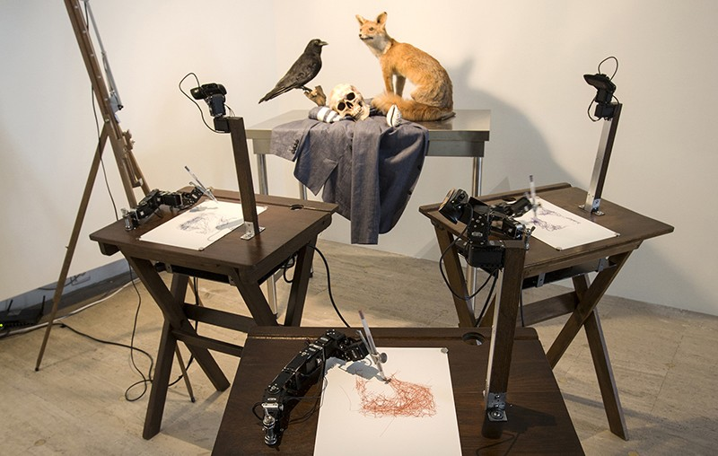 Three sets of robot arms and cameras on tables, drawing a still life of a stuffed fox, a stuffed raven and a human skull.