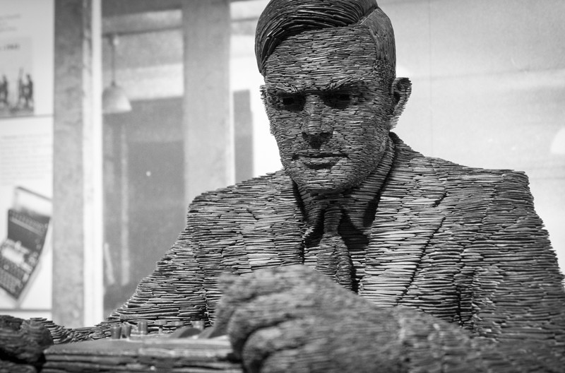 Statue of Alan Turing made of layers of stacked slate, shown from the chest up.
