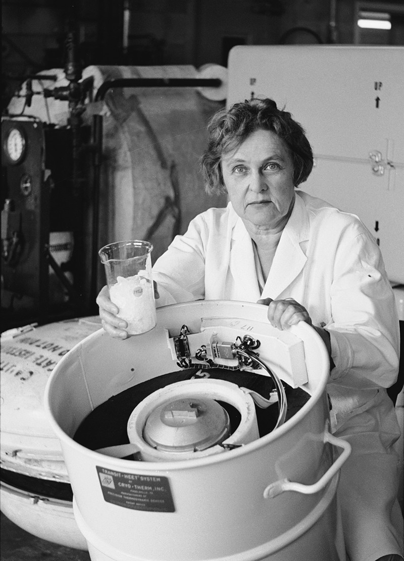 A white woman wearing a lab coat stands next to a large reaction vessel, holding a flask in one hand.