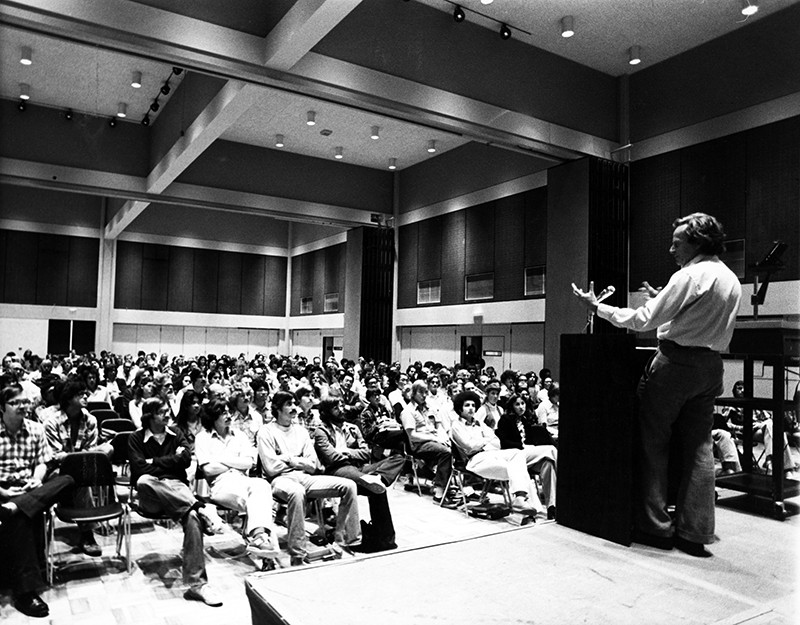 Black and white photo of Richard Feynman standing at a podium with his back to the camera, speaking to a room full of people.