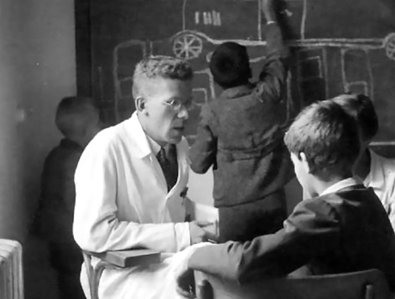 Black and white photo of Hans Asperger, in a lab coat, seated and talking to a boy. Other children write on a blackboard behind.
