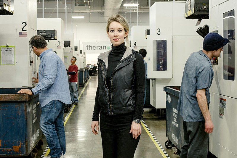 Elizabeth Holmes, a white woman dressed in black, stand between workers and machines in a biotechnology manufacturing facility.