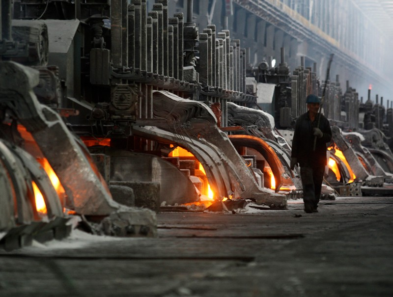 A worker walks through an aluminium smelting complex
