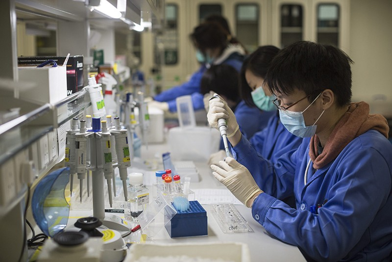 A team of scientists works at a lab bench