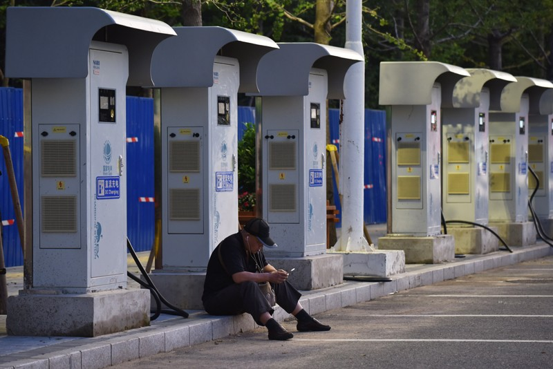 A man sits in front of unused electric car charging stations