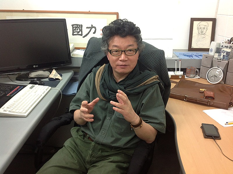 Professor Kue Y. Suh gesturing animatedly from a chair in his office. Copyright owner Kue Suh.