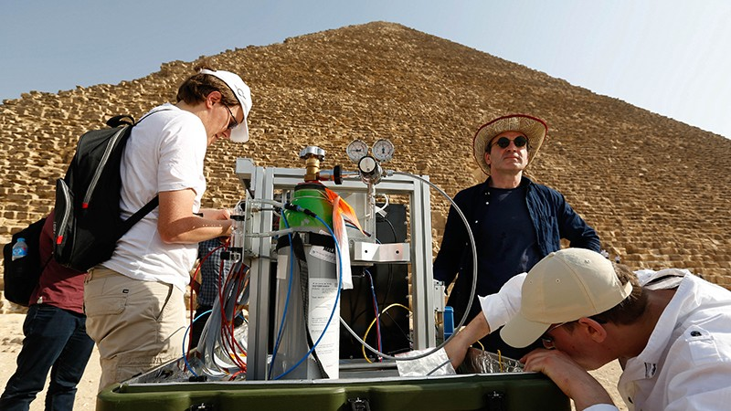 Researchers from pose a muon telescope in front of the north face of Khufu's Pyramid.