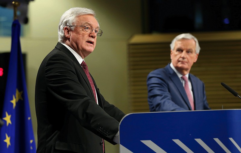 David Davis speaks as Michel Barnier watches during a press conference following Brexit talks in Brussels on March 19th 2018.