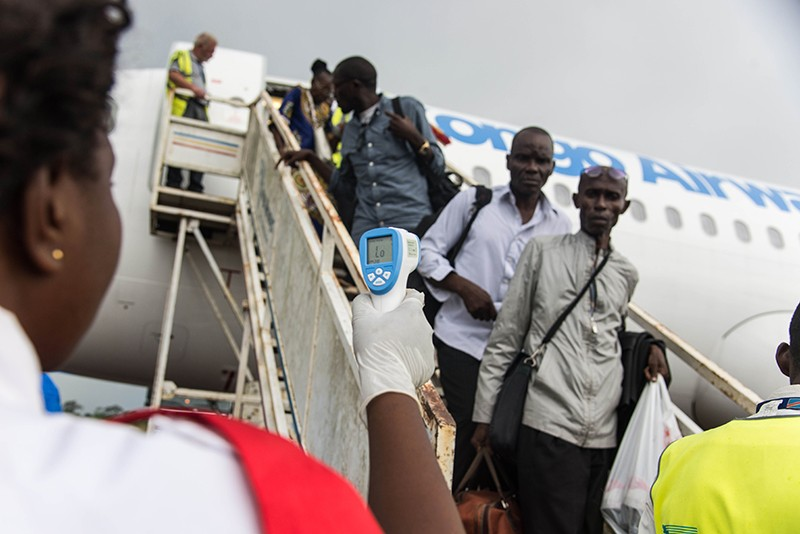 A health official uses a thermometer to measure the temperature of passengers disembarking a plane in DRC, May 2018