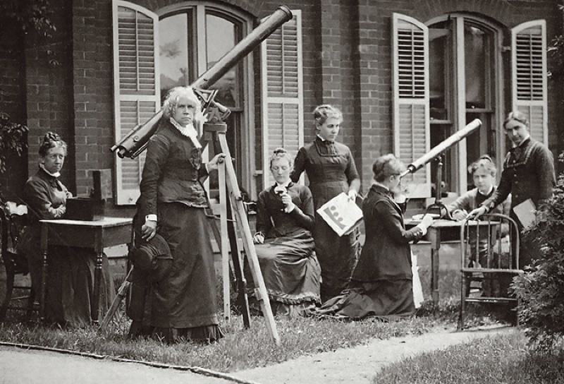 Photograph of Maria Mitchell and her students measuring the sun's rotation with small telescopes outside the old observatory.