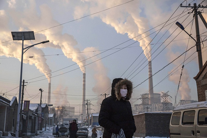 A woman walks near a coal-fired power station in Shanxi, China