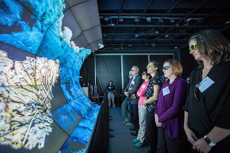 Users look at the 3D visualization system known as WAVE, used to explore ocean worlds