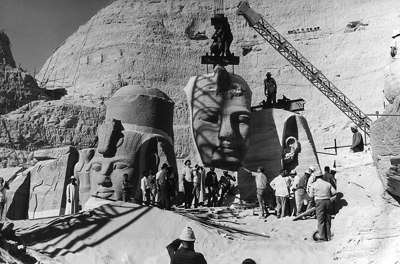 Worken lift the faces of huge statues on cranes in this black and white photograph from Abu Simbel.
