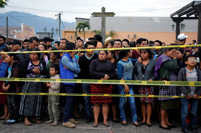 Residents stand behind a cordon after the Fuego volcano erruption