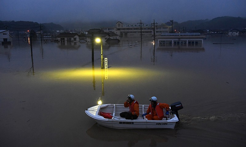 Fire fighters power their boat past a submerged streetlight at night on July 7th in Kurashiki, Japan