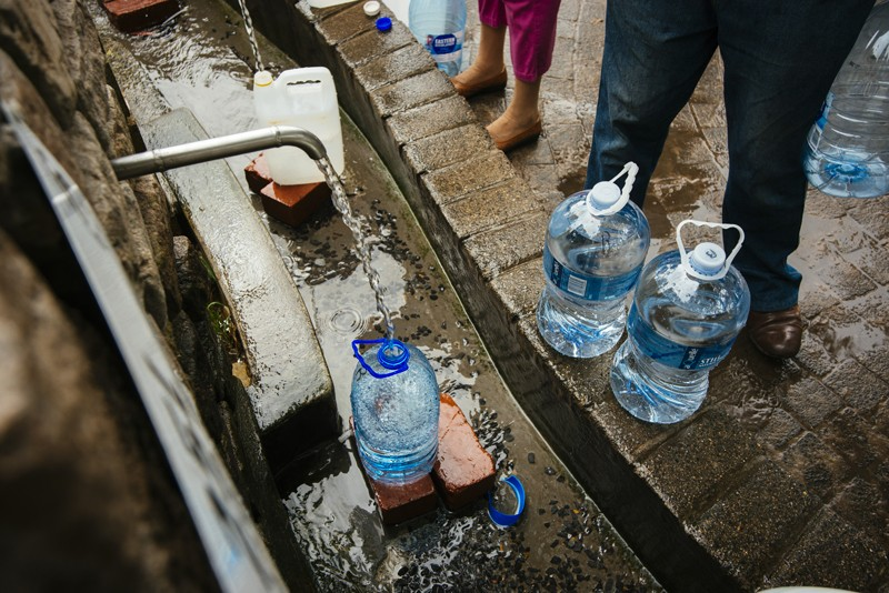 Residents fill water bottles at a natural water spring in Cape Town