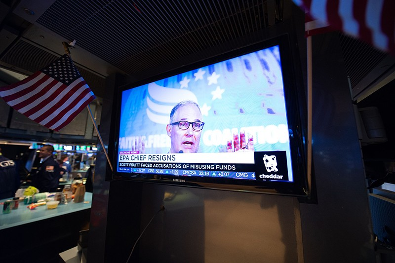 A television displays the news of Scott Pruitt resigning as head of the EPA on the floor of the New York Stock Exchange.