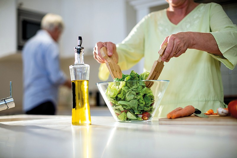 An older woman prepares a salad.